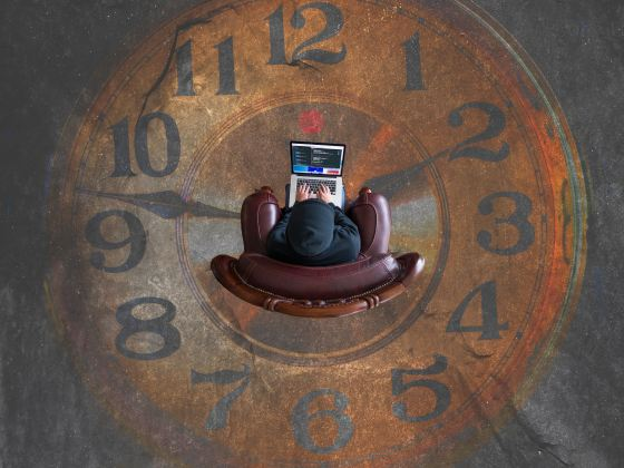 Image taken from above of a person with a laptop sitting on a chair, in the centure of a clock painted on the floor.